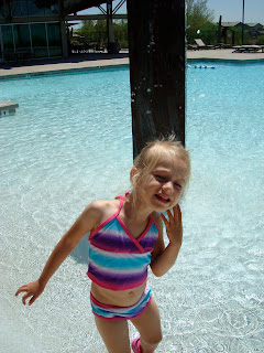 Young girl in bathing suit playing in pool