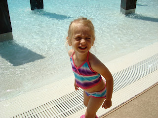 Young girl in bathing suit standing outside of pool