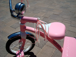 Close up of tassels on pink tricycle