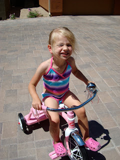 Young girl on tricycle smiling