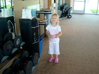 Young girl standing next to water cooler smiling