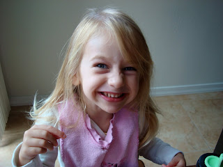 Young girl sitting at table eating and smiling
