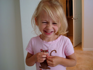 Smiling young girl wearing and holding necklace
