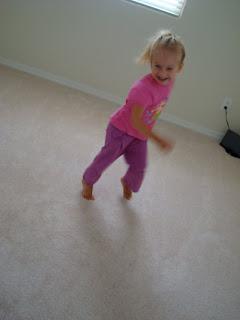 Little girl running around room smiling