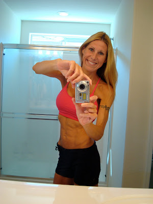 Woman in workout clothes showing off toned abs