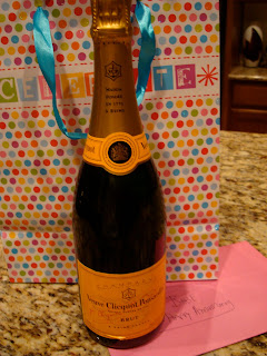 Bottle of champagne in front of gift bag