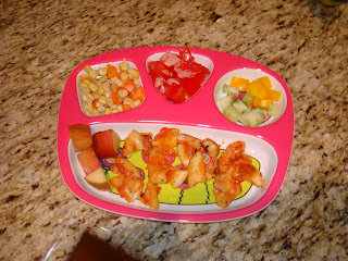 Child's plate with a mixture of fruit, vegetables and sliced up pizza