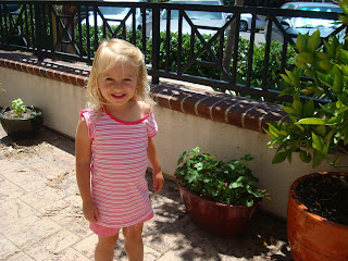Little girl smiling on balcony in front of plants