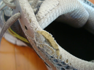 Side top of sneaker showing tear from running