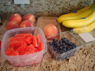 Peaches, watermelon, blueberries and bananas on countertop