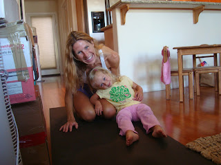 Woman and little girl smiling on yoga mat