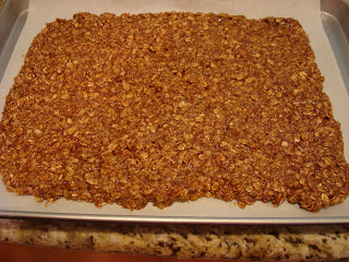 Homemade granola spread on parchment paper lined baking sheet