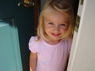 Little girl with door ajar smiling in pink shirt