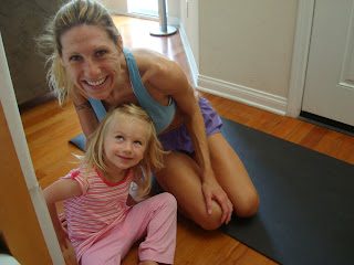 Woman and child on yoga mat smiling