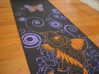 Black purple and orange yoga mat on wooden floor