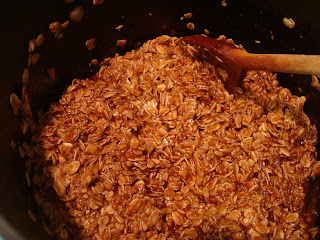 In process of making homemade granola in pan with spoon stirring