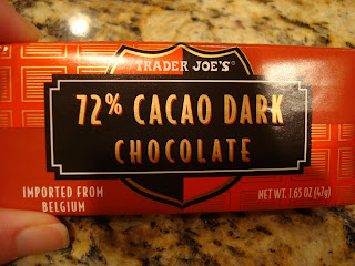 Hand holding Trader Joe's 72% Cacao Dark Chocolate Bar