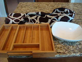 bamboo expandable silverware drawer organizer, white bowl and black and white towel on countertop