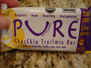 Hand holding Pure ChocChip Trailmix Bar in package