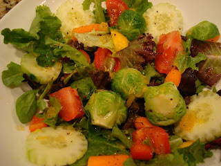 Mixed greens topped with vegetables and dressing in white bowl