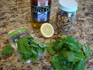 Pack of basil, spinach, olive oil, lemon and walnuts on countertop