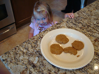 "Young girl smiling next to Maple & Flax ""Peanut Butter"" Pancake-Cookies on countertop"