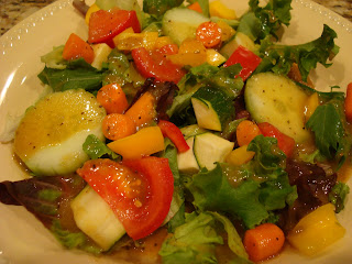 Mixed greens and vegetables in white shallow bowl