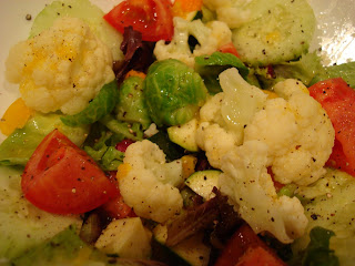 Mixed greens and vegetables in bowl topped with dressing