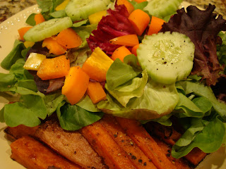Mixed vegetable salad served with sweet potato fries on white plate