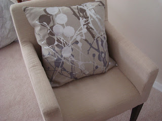 Tan chair with neutral accent pillow on chair