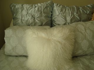 Pillows on bed with white fluffy pillow in front