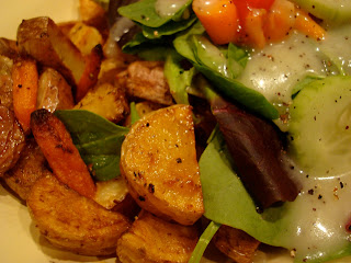 Close up of the roasted potatoes and carrots next to dressed salad