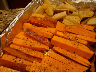 Sliced Sweet Potatoes and White Potatoes oiled and seasoned in foil lined pan