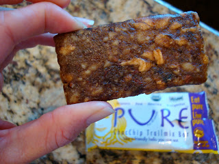 Hand holding Pure Brand Chocolate Chip Trail Mix Bar