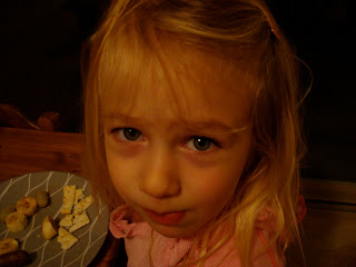 Close up of young girl eating snacks off of plate