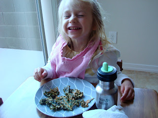 Young girl smiling at table eating Kale Chips