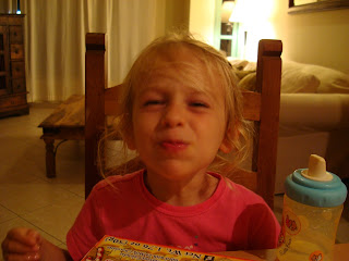 Little girl sitting in chair making funny face