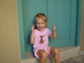 Young girl sitting in front of blue door smiling