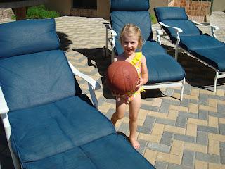 Little girl holding basketball poolside