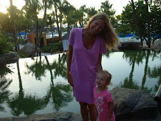 Woman and young girl at dusk standing in front of pool