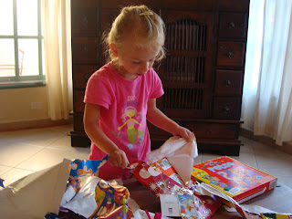 Young girl opening up presents on floor
