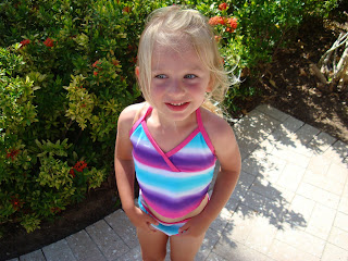 Young girl in bathing suit standing in front of bush