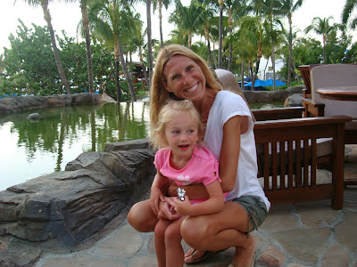 Woman hugging young girl in front of water feature