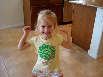 Young girl in yellow shirt flexing