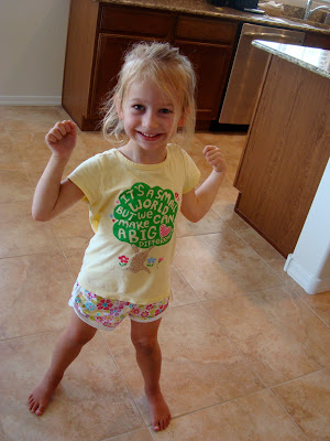 Young girl standing in kitchen flexing
