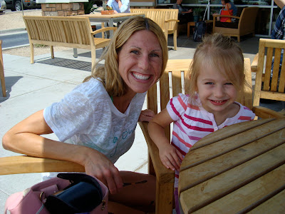 Woman crouching next to young girl at table smiling