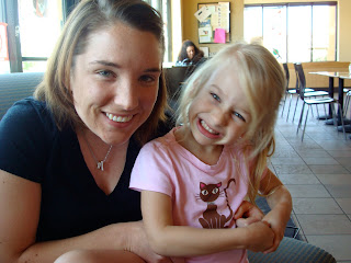 Woman in black shirt with young girl sitting on her lap smiling