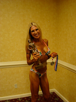 Woman in bikini holding trophy and medal