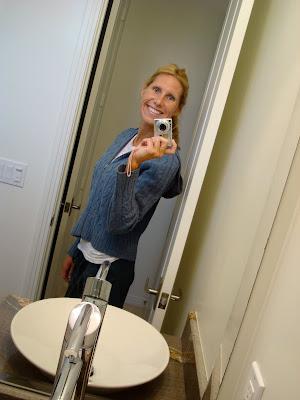 Woman taking photo of self in door way smiling