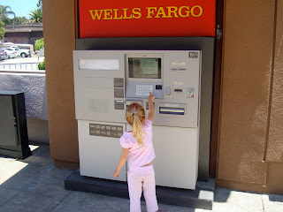 Young girl playing with ATM machine